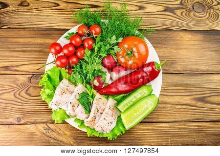 Plate with sliced fresh pork lard fresh produce vegetables on the wooden table top view