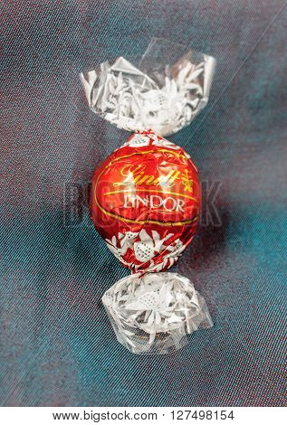 KILCHBERG SWITZERLAND - MARCH 20 2014: Lindt Lindor chocolate truffle on a chameleon luxury silk background. Lindt is one one of the lastgest luxury chocolate and confectionery company worldwide with more than 30 factories worldwide