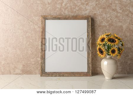 Blank Picture frame on the wall a vase of sunflowers