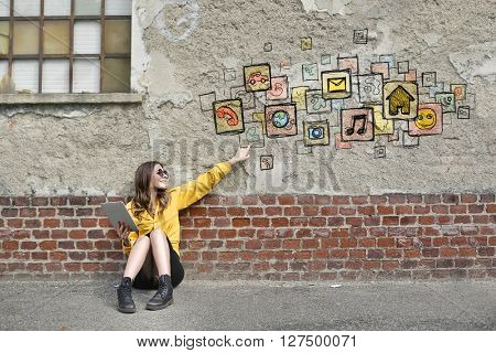 Technological woman sitting on the ground