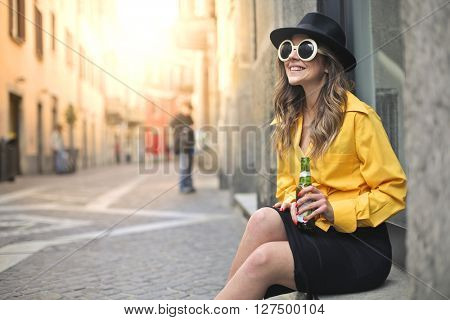 Happy woman sitting outdoors with a beer