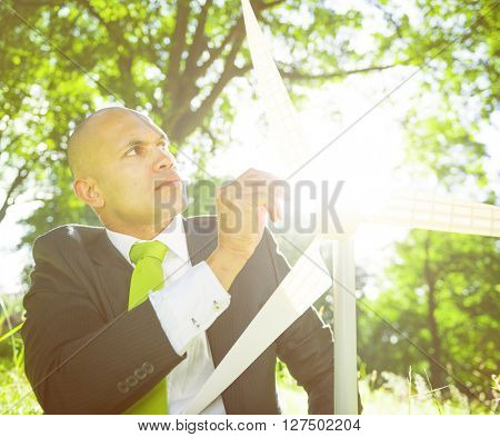 Businessman holding wind turbine in the woods.