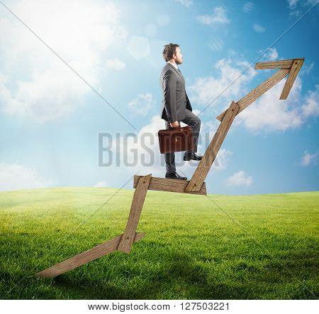Confident man climbing an arrow of wood