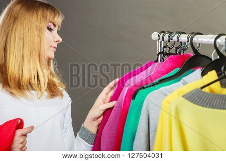 Pretty happy woman watching clothing from new collection wardrobe. Young undecided shopper girl choosing which clothes to wear. Shopping sale concept.