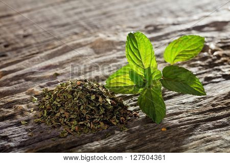 Heap of dry mint and fresh on wooden table