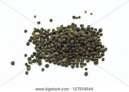 Stack of dry black pepper on white background