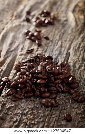 Heap of fresh brown coffee beans on wooden table