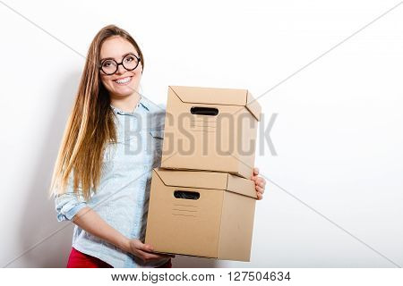 Happy woman moving in carrying cartons boxes. Young girl arranging interior and unpacking at new apartment house home.