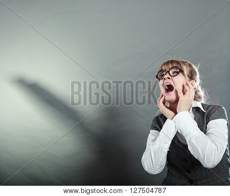 Business woman screaming looking upward in full fear wide open mouth grey wall background.