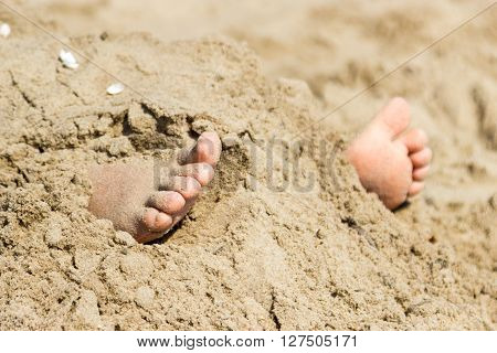 Human Feet Buried In Sand. Summer Beach.