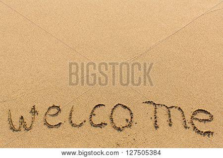 Welcome - hand-written on sandy beach.