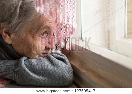 An elderly woman sadly looking out the window, face close-up.