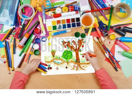 child drawing kitchen garden with vegetables , top view hands with pencil painting picture on paper, artwork workplace