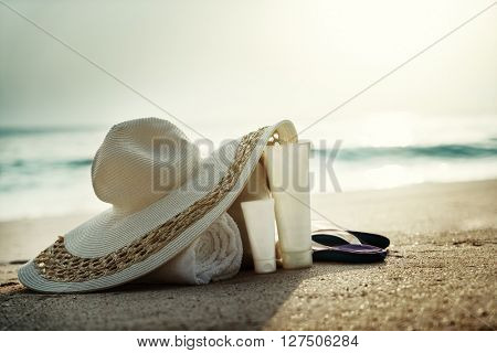 Sun lotion, hat  with bag at the tropical beach