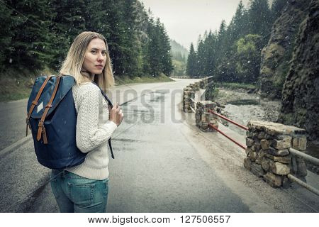 Woman hiking around mountains at spreeng time but under snow.
