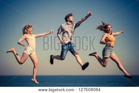 Carefree Friends Jumping By Sea Ocean Water.