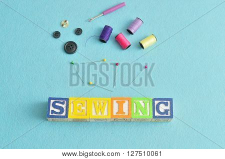The word sewing spelled with colorful alphabet blocks displayed with spools of thread and various sewing equipment on a blue background
