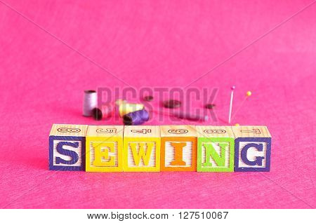 The word sewing spelled with colorful alphabet blocks displayed with spools of thread and various sewing equipment that is out of focus against a pink background