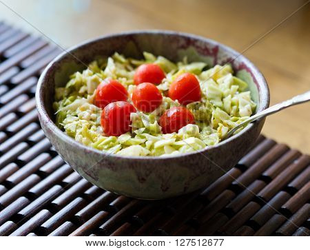A bowl of homemade coleslaw with cherry tomatoes