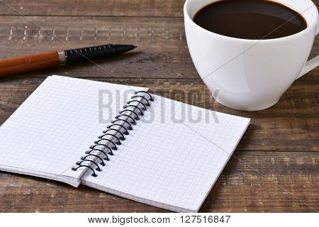 a blank notebook, a pen and a cup of coffee on a rustic wooden table