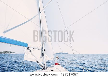 Young woman wearing red shorts, sitting on deck under sails on yacht bow and enjoying wonderful view to islands in peaceful sea during summer sailing holidays - yacht charter concept