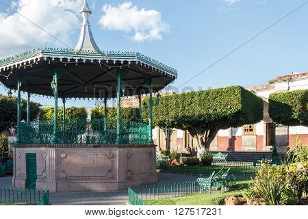 A gazebo at a plaza with trees cut into square shapes in Quiroga Michoacan Mexico