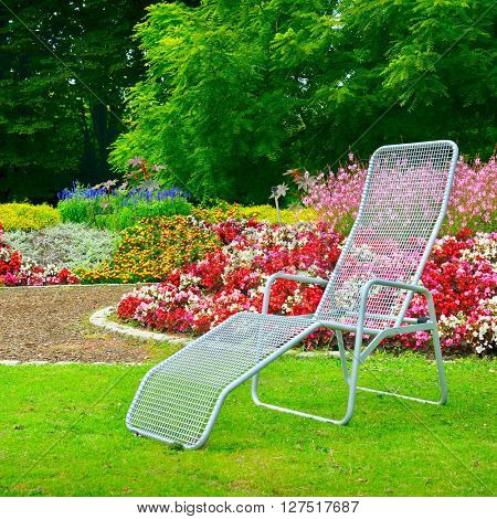 deckchair in park next to the flower bed