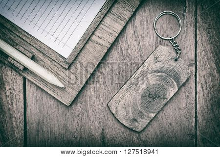 wooden signs with key chain and paper notes on wooden background.