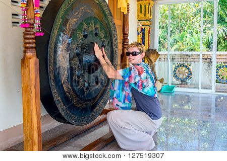 Big gong in a buddist temple where you could see how clean is your karma. It is sayd that if a person has a pure karma - the gong will emit a loud buzz. Tourist woman checking her karma.