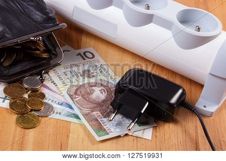 Electrical power strip with disconnected plug and polish currency money with black leather pocket purse concept of saving money on electricity