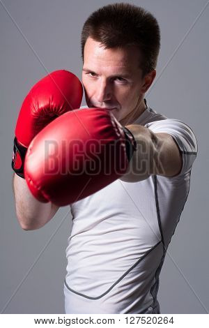 Boxer in attack position on a gray background