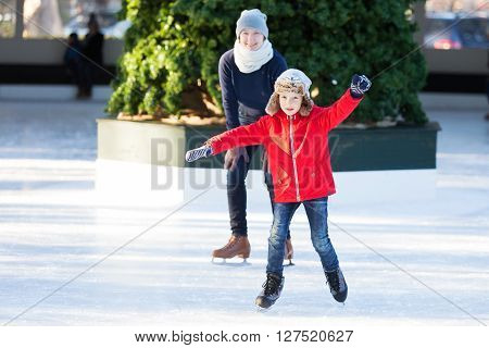 little boy learning ice skating and his mother watching and cheering up at outdoor skating rink having winter vacation fun