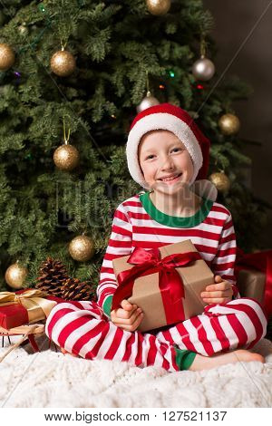 joyful smiling child in santa's hat holding nicely wrapped present and being cozy at home and enjoying christmas time by the tree and decorations
