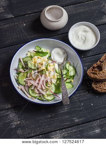 Salad with smoked turkey cucumber and boiled egg on a dark wooden background. Healthy food
