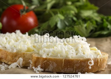 Slice of bread with butter and grated cheese and tomato with parsley in background