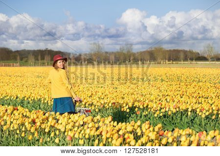 Smiling woman standing with her bike in a yellow and red tulips field at sunset.
