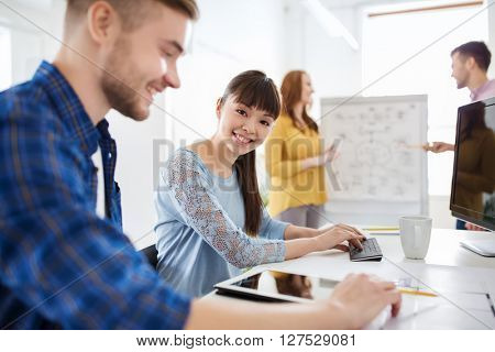 business, startup and people concept - happy creative team with tablet pc computer at office