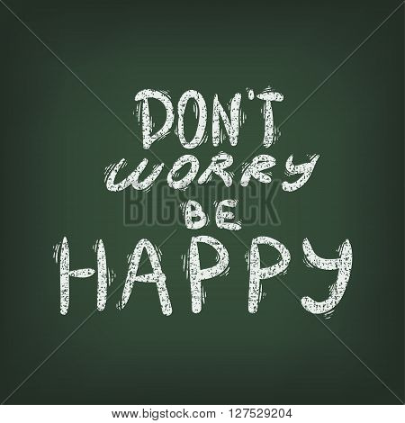 Don't worry be happy - handwritten lettering by chalk on a green board.