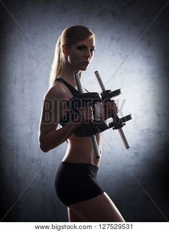 Beautiful woman having a dumbbell training in the underground gym.