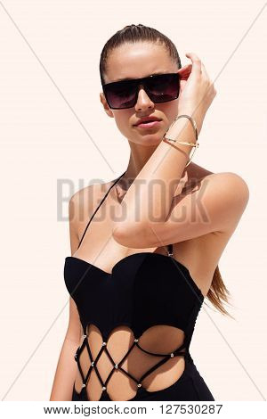 Woman in black sunglasses and swimsuit wearing golden bracelet with hair up poses on isolated white background. Fashion tan model. Beautiful awesome cool girl. Phuket, Thailand