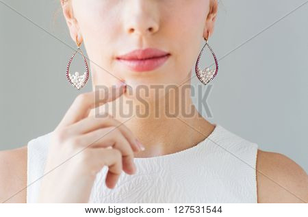 glamour, beauty, jewelry and luxury concept - close up of beautiful woman face with pearl earrings