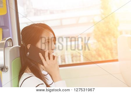 Woman talk to mobile phone inside train station