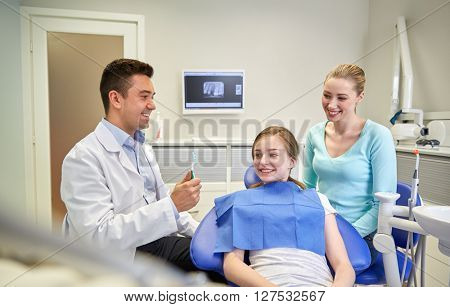 people, medicine, stomatology and health care concept - happy male dentist showing toothbrush to patient girl and her mother at dental clinic office