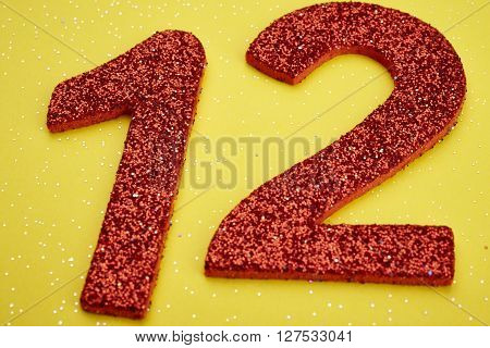 Number twelve red color over a yellow background. Anniversary. Horizontal