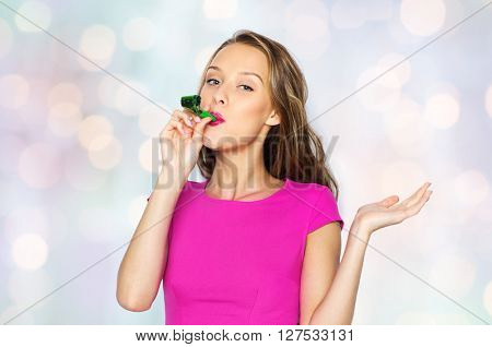 people, holidays and celebration concept - happy young woman or teen girl in pink dress and party cap over holidays lights background