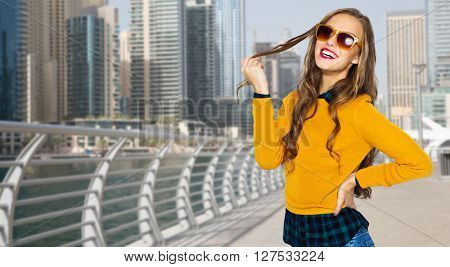 people, travel, tourism, style and fashion concept - happy young woman or teen girl in casual clothes and sunglasses over dubai city street background