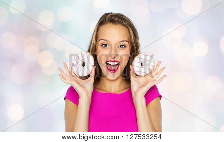 people, holidays, junk food and fast food concept - happy young woman or teen girl in pink dress with donuts over holidays lights background