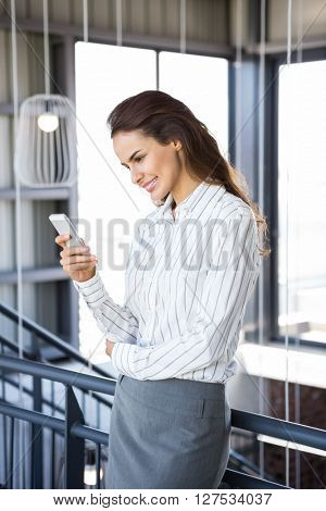 Portrait of young businesswoman using mobile phone in office