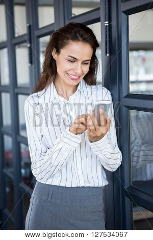 Beautiful young businesswoman using mobile phone leaning on office door