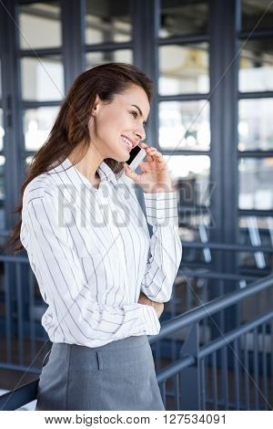 Beautiful young businesswoman using mobile phone in office